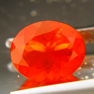 translucent untreated faceted orange-red fire opal in oval shape